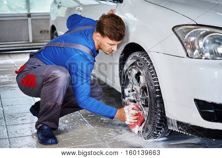 Man worker washing car's alloy rims on a car wash.