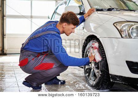 Man worker washing car's alloy rims on a car wash.
