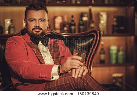 Extravagant stylish man with whisky glass sitting on armchair in gentleman club.