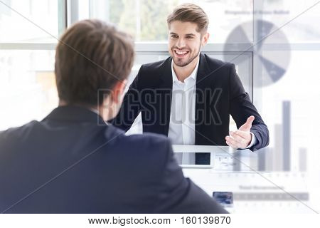 Double exposure of Two cheerful young businessmen using tablet and working together on business meeting in office