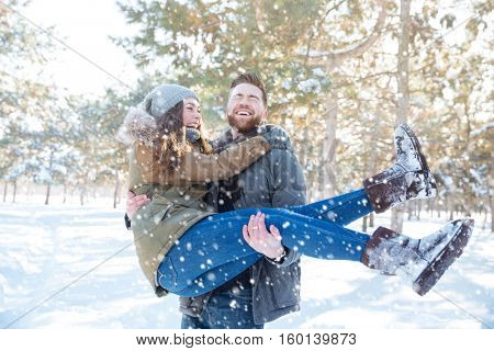 Happy man holding his girlfriend on hands in winter park
