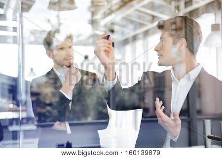Two concetrated young businessmen talking and writing on glass board in office