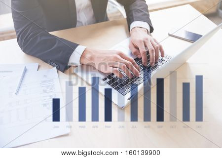 Double exposure of Closeup of hands of young businessman working using laptop in office