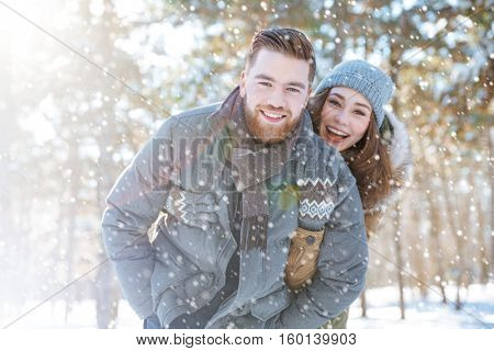 Smiling young couple looking at camera in winter park