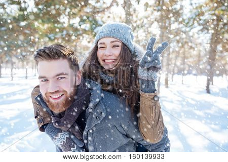 Happy young couple walking in winter park and showing victory sign at camera