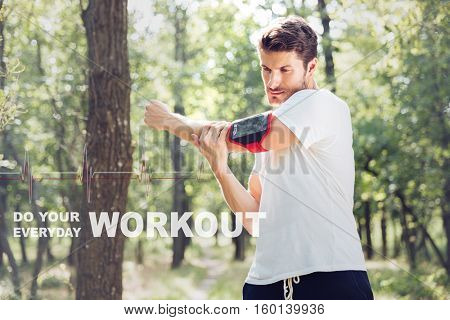 Athletic young sportsman with mobile phone in handband standing and doing exercises in forest. Do your workout everyday