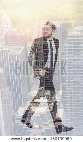 Full length double exposure of bearded businessman walking with arms in pockets and looking back. Side view