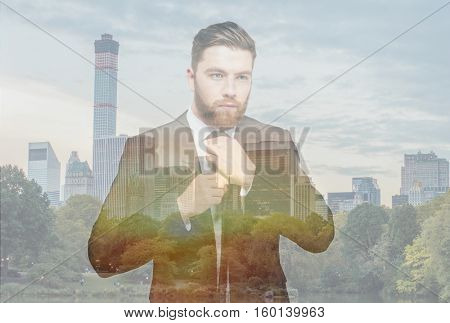 Double exposure of bearded serious businessman on cityscape tying a tie and looking aside