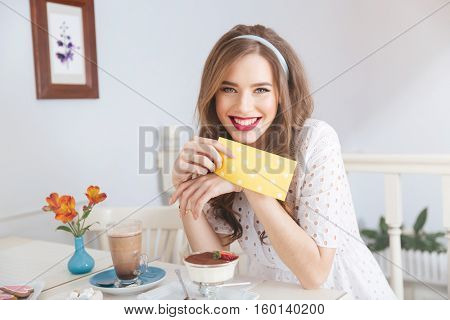 Cheeerful attractive young woman in white dress drinking latte and eating dessert in cafe