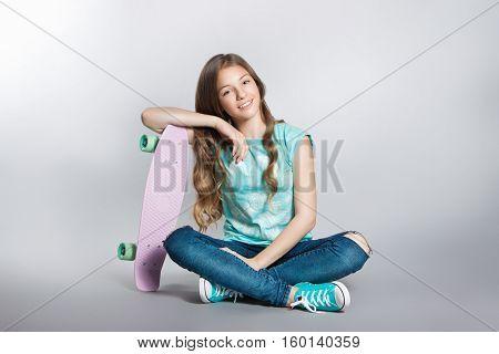 Girl Posing With Skateboard Sitting In The Studio. Joy, Smile, Positive Emotions