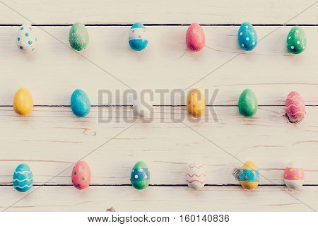 Colorful easter eggs and hand paint on wooden background. background with space.