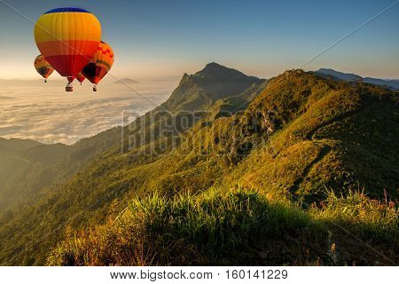Colorful hot air balloons flying over on Pha Tung mountain in sunrise time Chiang Rai Thailand.