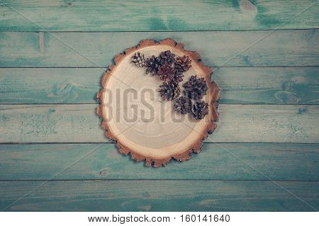 Circle wooden board dry pine cones on blue wooden table