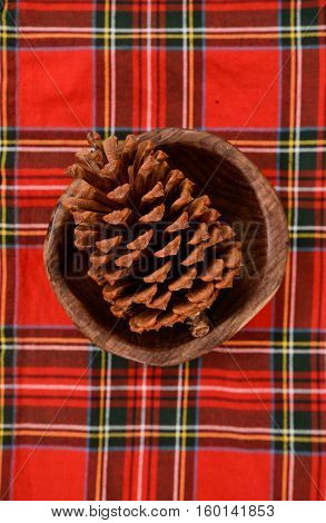 Fir Cones in bowl on Red picnic texture