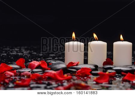 Still life with many red rose petals with three candle and therapy stones