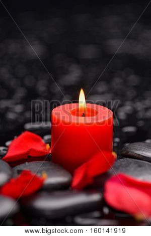 rose petals with red candle and therapy stones