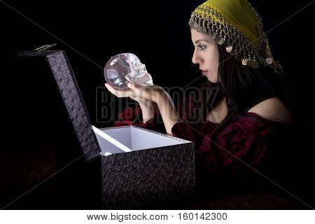 Fortune teller or gypsy opeing a glowing mysterious box and discovering treasure. She is receiving a magical gift or a treasure chest or package.