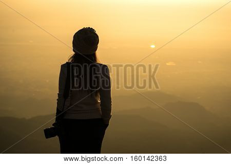 Silhouette of a woman photographer standing in dry grass field on sunrise