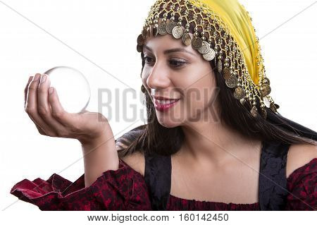 Close up of female fortune teller or psychic with clear crystal ball for composites. Facial expressions indicate she is seeing a vision on in the orb.