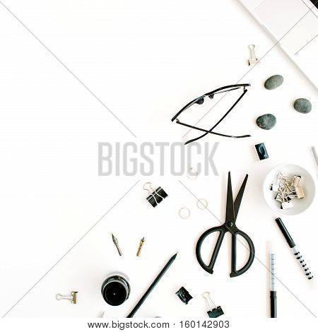 Flat lay top view office table desk. Workspace with laptop scissors glasses pen on white background.
