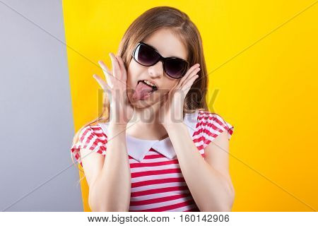 Pretty Girl In Sunglasses Posing On A Yellow-gray Background. Bright Stock Photos. Positive Human Em