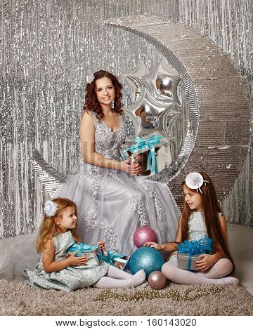 Mother and daughters are waiting for Christmas. Mom dressed fairy fairies. Girls sit on the floor and play with Christmas decorations balls and gifts. Happy parenting and childhood. Family holidays.