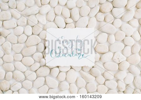 Inspirational quote on neutral pattern of beige stones. Flat lay top view