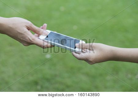 mother giving her child a mobile phone