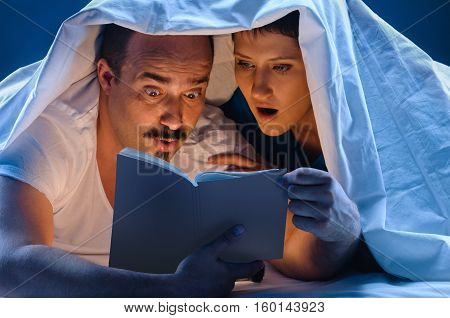 Young man and woman lying down on white sofa. reading book. and blue night light background