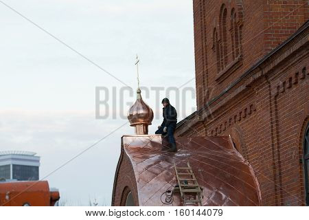 KAZAN, RUSSIA, 19 NOVEMBER 2016, Roofer repairing roof of ortodox Old believers ' Church in winter cold day, horizontal