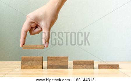 Hand arranging wood block stacking as step stair. Business concept for growth success process
