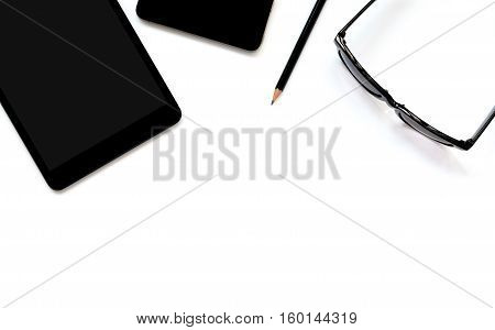 Flat lay photo of office desk with tablet smartphone eyeglasses and pencil with copy space background