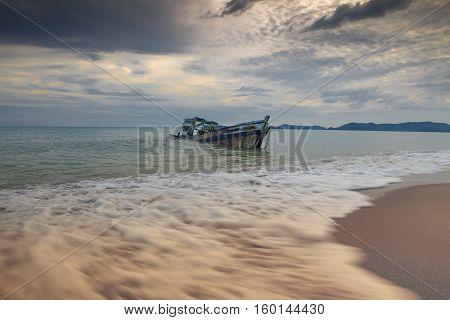 seascape of wreck boat on sea beach