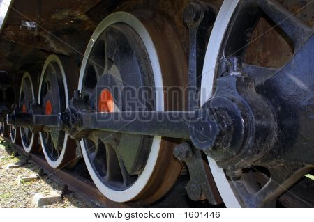 Closeup sideview of an old trains wheels poster