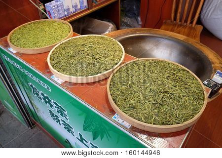 HANGZHOU - FEBRUARY 21: Various types of tea in wooden bowls exposed for sale in a Chinese tea shop in Hangzhou, China, February 21, 2016.