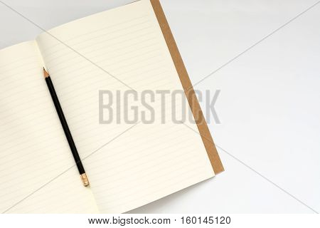 Flat lay photo of office desk with open book and pencil with copy space background
