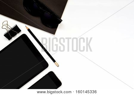 Flat lay photo of office desk with tablet smartphone sun glasses black book paper clip and pencil with copy space background
