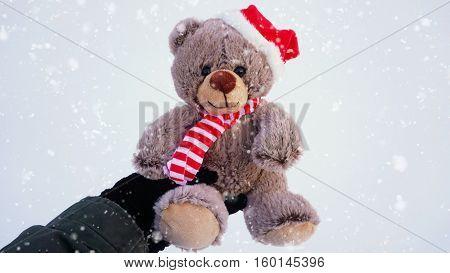 Female hand holding a cute Christmas teddy bear against snow on the ground with snowfall effect