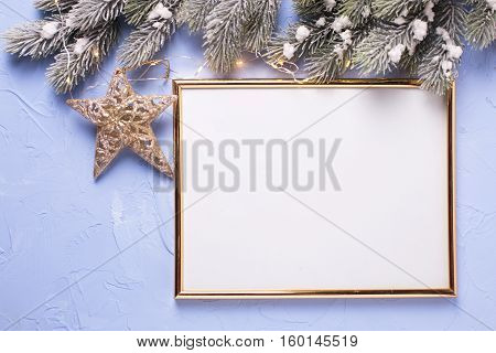 Empty frame christmas star branches fur tree and fairy lights on blue textured background. Decorative christmas composition. Place for text.