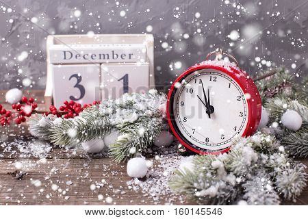 Vintage red clock calendar branches fur tree and red berries on aged wooden background. Selective focus. Drawn snow.