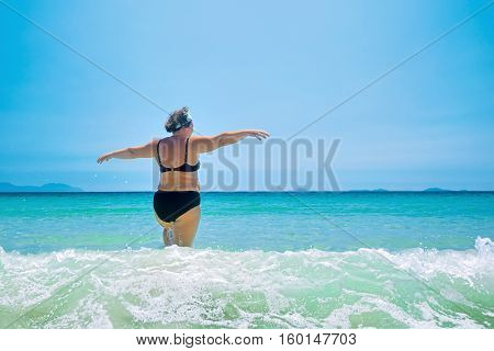 mature woman in swimwear at the sea. Overweight woman in swimsuit comes in water in time of surf rear view
