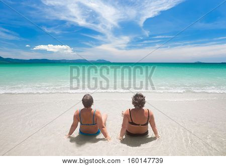 mature woman in swimwear relaxing on the beach. Relaxed senior caucasian woman outdoors