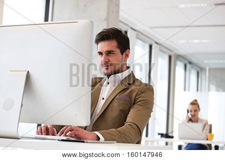 Confident young businessman working on computer with female colleague in background at office