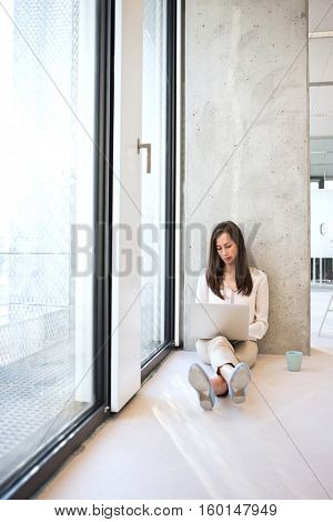 Full length of young businesswoman using laptop by office window