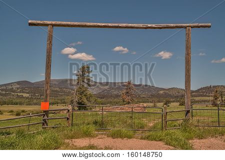 Entrance to a ranch with mountains and a blue sky in the background