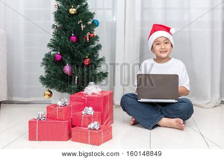 Asian Chinese Little Boy With Laptop Beside Christmas Presents