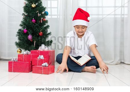 Happy Asian Chinese Little Boy Reading Book Beside Christmas Presents