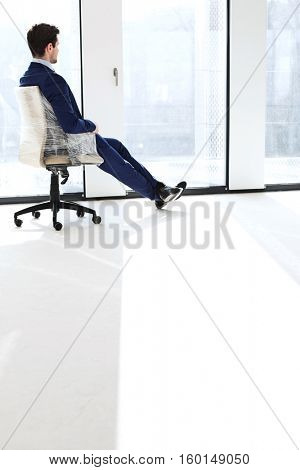 Full length side view of thoughtful young businessman sitting on chair by windows in office