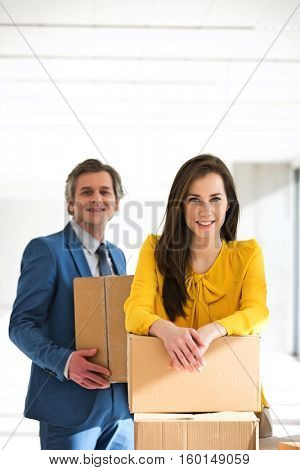 Portrait of businesswoman and male colleague with cardboard boxes in new office