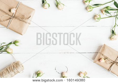 Spring flowers. Gift and rose flowers on wooden white background. Top view flat lay